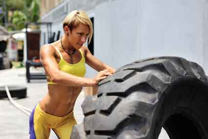 Athlete female working out with a huge tire, turning and flippin