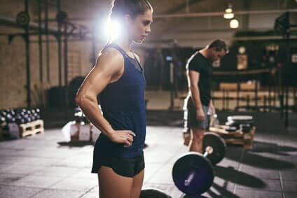 fitness mann und frau neben langhanteln
