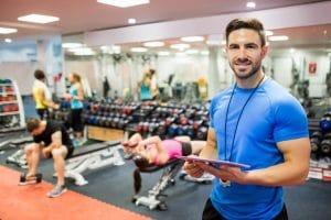 Fitnesstrainer im Gym mit Tablet