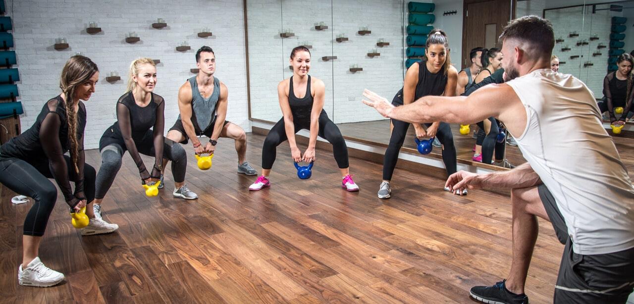 Gruppe beim Kettleballtraining mit Fitnesscoach
