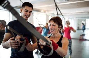 junger Fitnesscoach erklärt Übungen